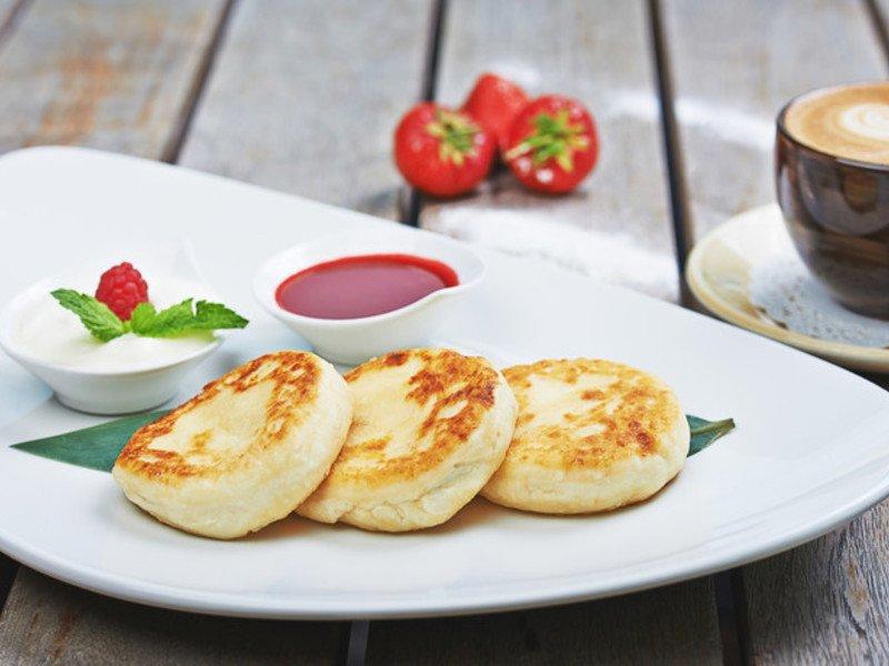 Диетические сырники на белом блюде, сметана и джем