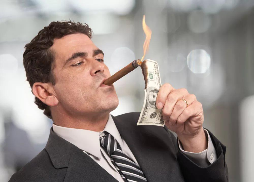 Мужчина подкуривает сигару от горящей долларовой купюры