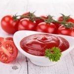 Кетчуп в белой пиале и томаты