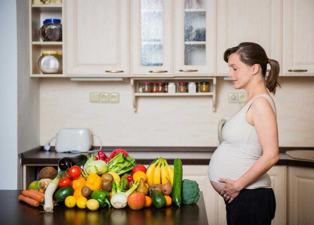 Беременная женщина стоит перед столом, полном овощей и фруктов