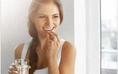 Девушка пьёт витамины