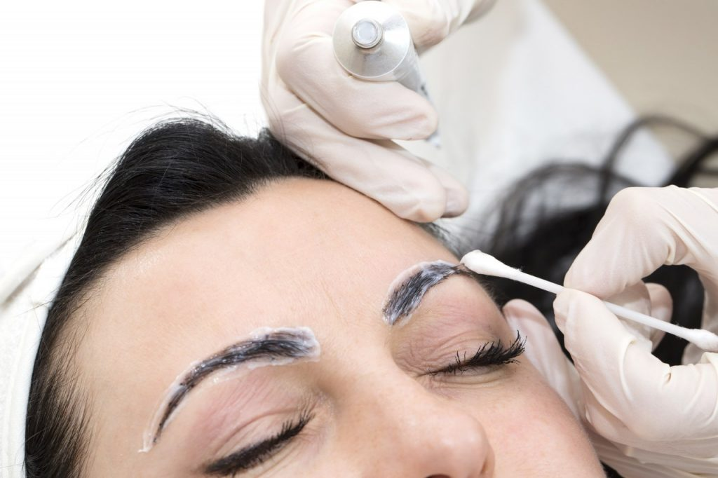 Нанесение ранозаживляющей мази на брови девушки после татуажа