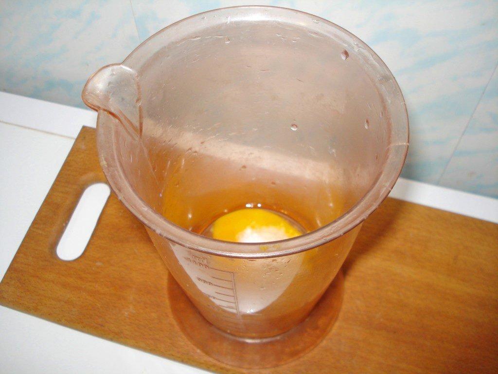 Сырое яйцо в пластиковом мерном стакане