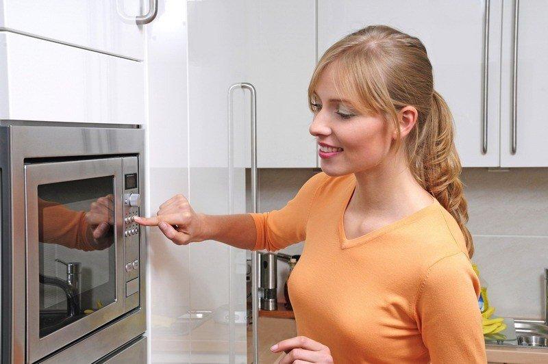 Женщина готовит в микроволновке