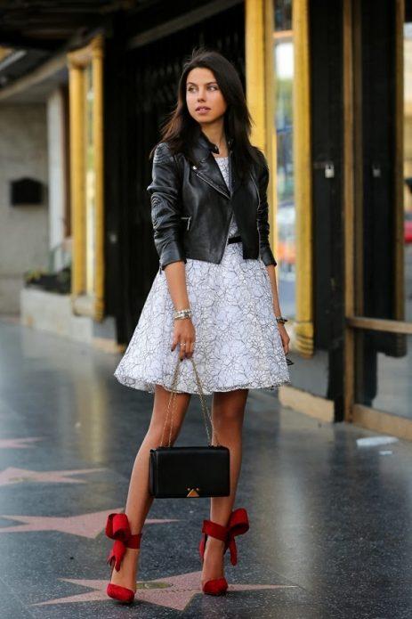 Красные туфли на каблуке с бантами под белое платье с узором и черную кожаную куртку