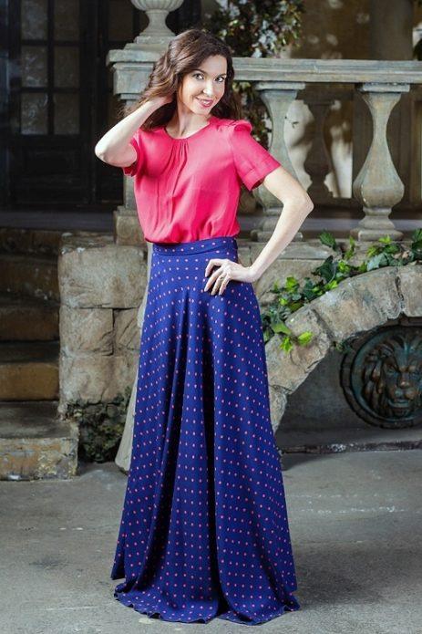 Девушка в ярко-розовом шифоновом топе и синей юбке в горошек в пол