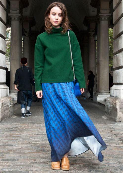 Девушка в темно-зеленом свитере и синей юбке в пол с узорами