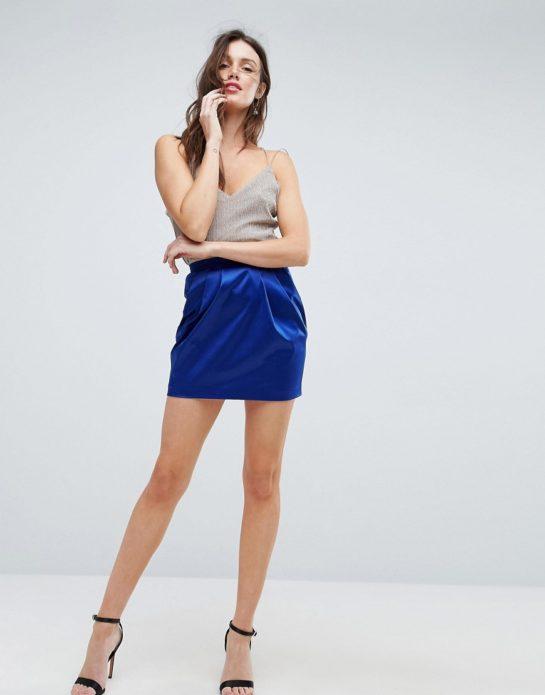 Бежевый топ с вырезом, атласная синяя юбка мини и черные босоножки на шпильке
