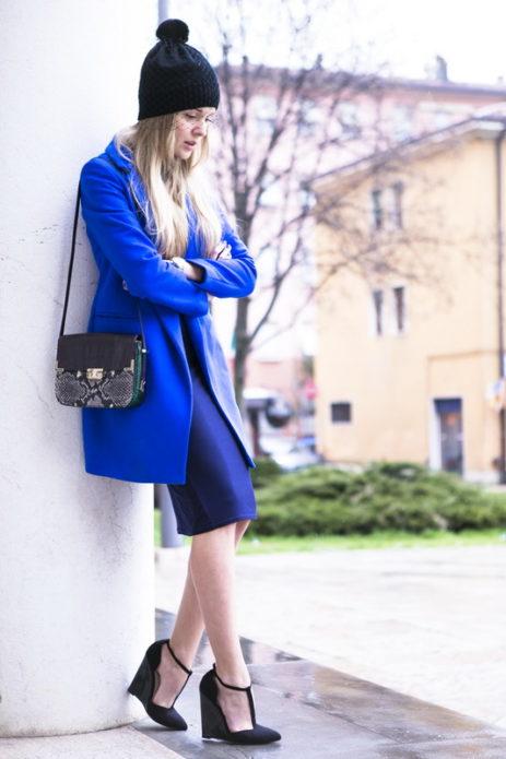 Девушка в синем тренче и юбке, с черной шапкой, сумочкой и туфлями на платформе