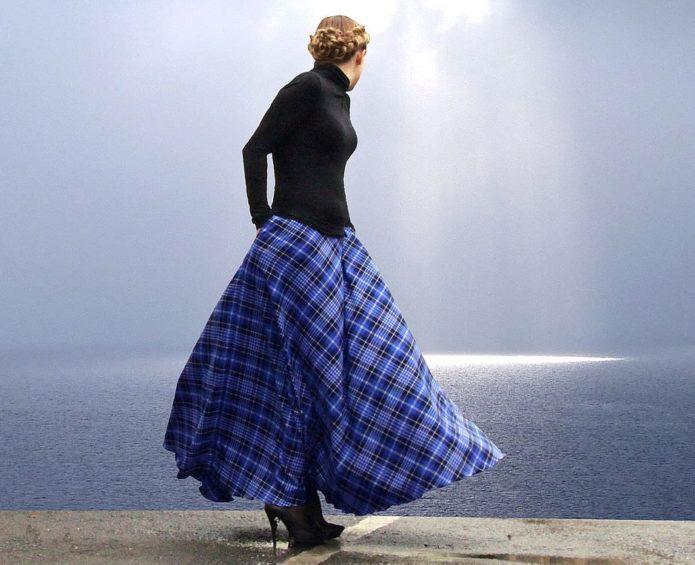 Девушка в черной водолазке и туфлях с синей летящей юбкой в клетку