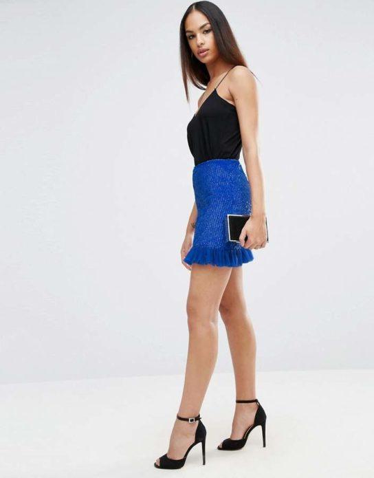 Черный топ, синяя юбка мини, черные клатч и босоножки на каблуке