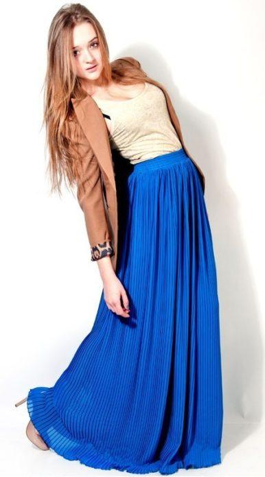 Девушка в бежевой футболке, коричневом жакете и плиссированной синей юбке в пол