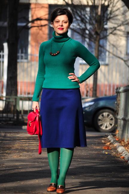Девушка в зеленой водолазке в рубчик, синей юбке миди, зеленых колготках и с красной сумкой