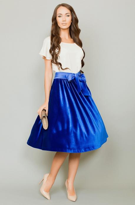 Девушка в синей атласной юбке миди, белом топе и бежевых туфлях