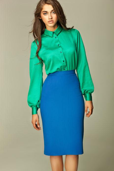Девушка в длинной изумрудной рубашке из атласа и синей юбки миди