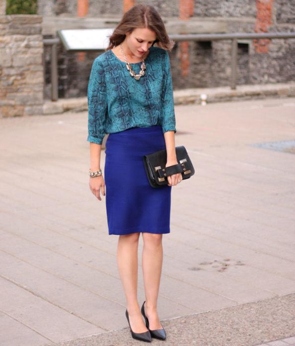 Девушка в бирюзовой кофие и синей юбке миди с черным клатчем и туфлями на шпильке