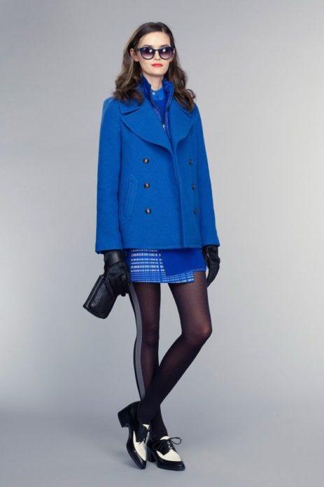 Девушка в синем пальто и юбке, черных колготках в полоску, в перчатках, с клатчем и в черно-белой обуви