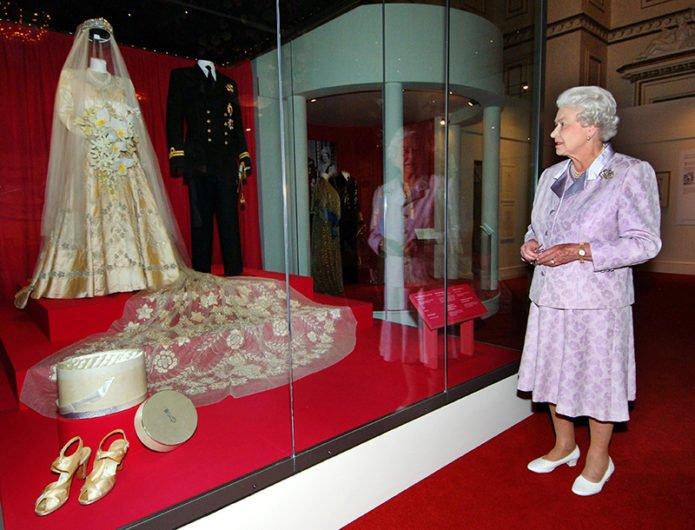 Королева Елизавета рядом со свадебными нарядами