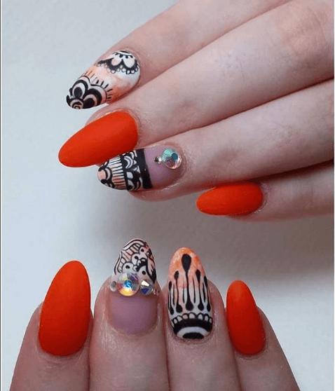 Оранжевый маникюр с черно-белыми узорами и стразами