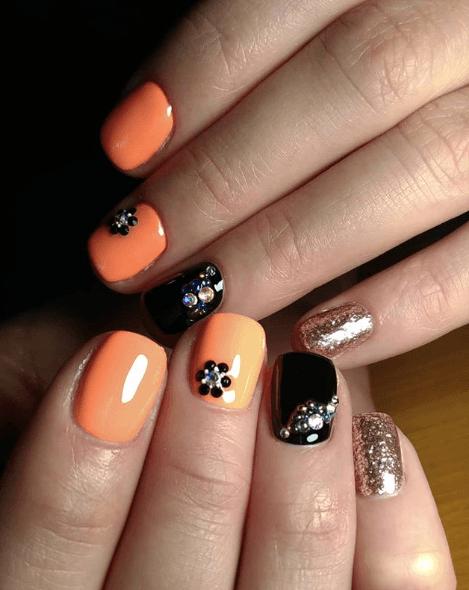Оранжевый маникюр с черным, камнями и золотыми блестками