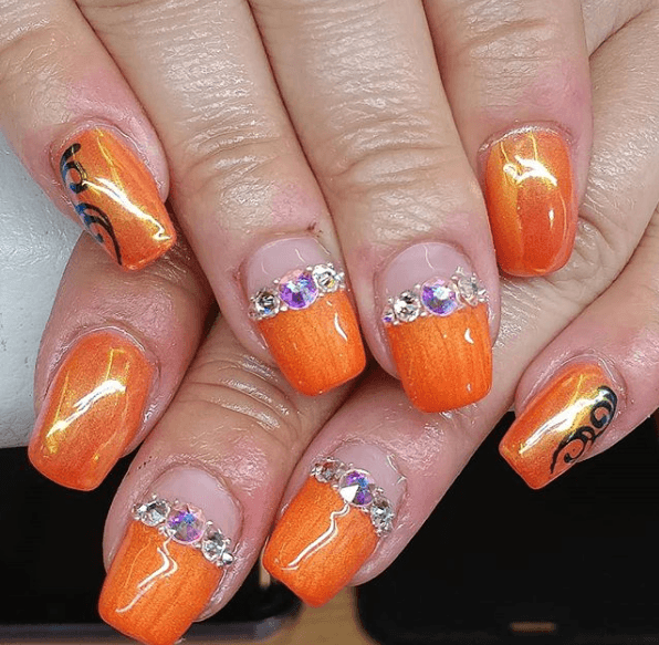 Оранжевый маникюр с черными узорами и камнями