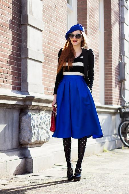 Девушка в черно-белой кофте с черным жакетом в синей юбке миди и с беретом в колготках в горошек