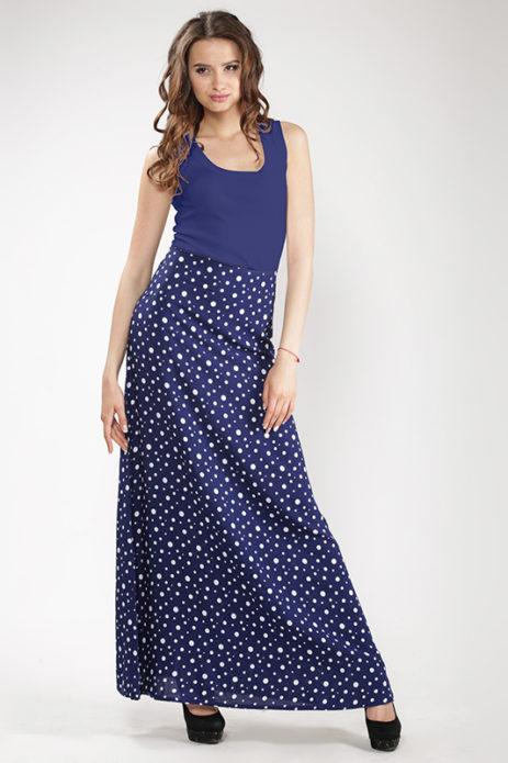 Девушка в матово-синем топе и длинной синей юбке в белый горошек
