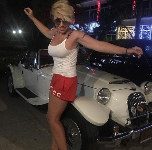 Елена Воробей в шортах и майке на фоне машины
