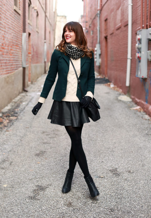 Образ из тёмно-зеленого пиджака, черной кожаной юбки клеш мини, черной сумки, перчаток и колготок с клетчатым черно-белым шарфом и черными ботильонами