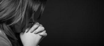 Женщина сложила руки замком и держит перед губами