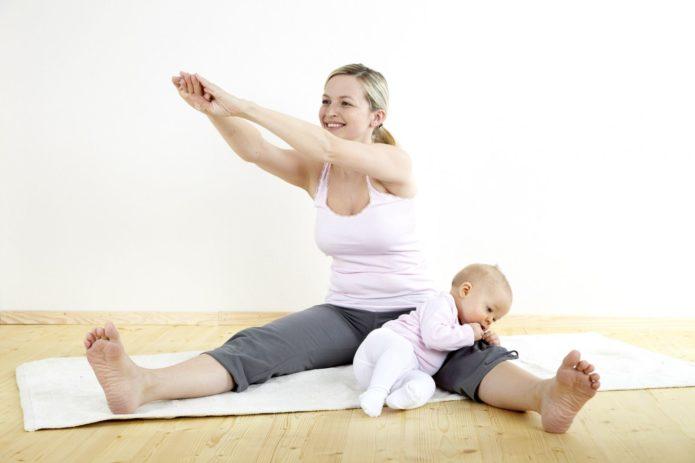 Девушка занимается гимнастикой с маленьким ребёнком, опирающимся на её ногу