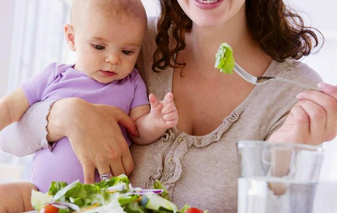 Женщина держит на руке ребёнка и ест салат