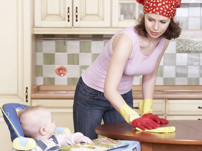 Женщина вытирает стол, рядом сидит малыш