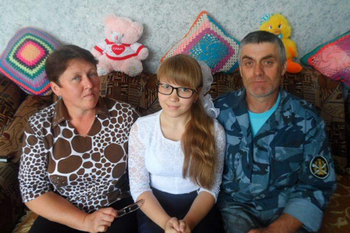 Родители сидят на диване с дочкой