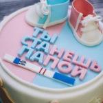 Розово-голубой торт, украшенный пинетками, тестом на беременность и надписью «Ты станешь папой»