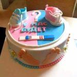 Розово-синий торт, украшенный пинетками, тестом на беременность и надписью «У нас будет»