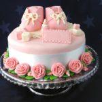 Торт, украшенный розовыми пинетками и розами