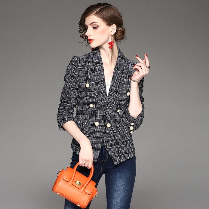 девушка в твидовом пиджак, сумочка, серый фон