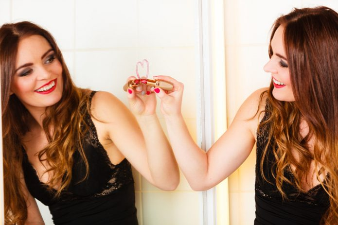 Девушка рисует помадой на зеркале