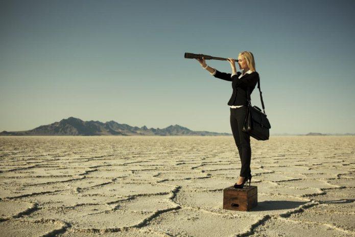 Девушка смотрит в подзорную труду в пустыне