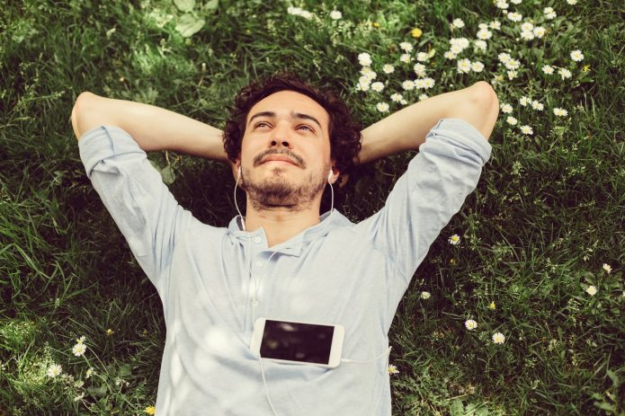 Мужчина лежит на газоне и мечтает
