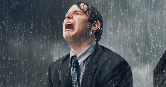 Мужчина рыдает во время дождя