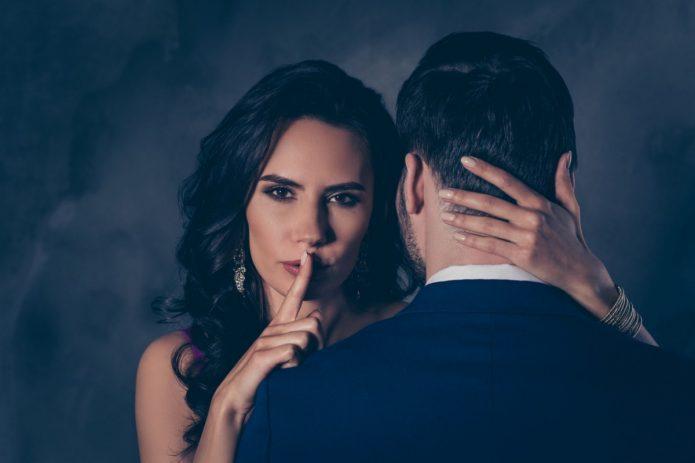 Девушка, обнимающая парня, прижимает палец к губам