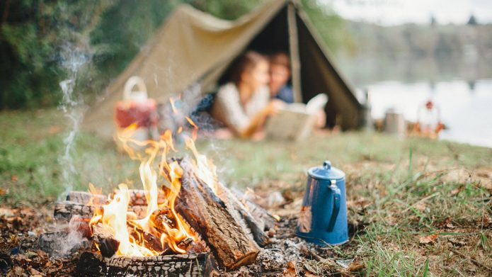 парень и девушка в палатке на фоне костра