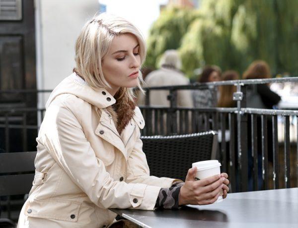 Девушка задумчиво пьет кофе
