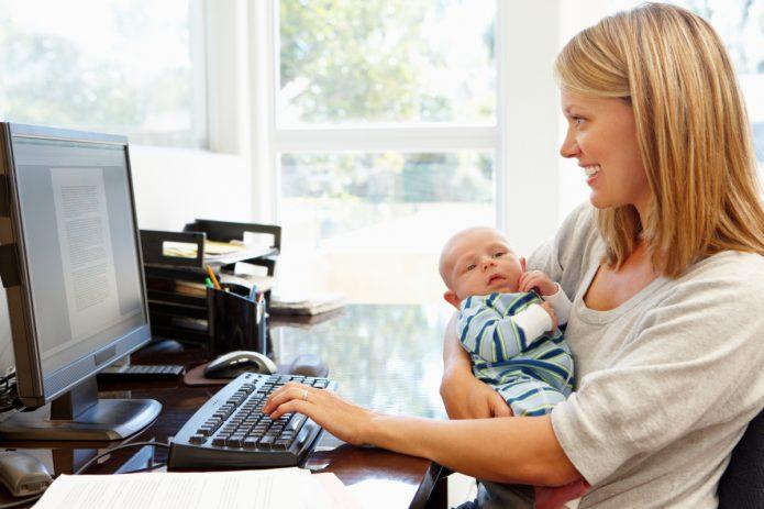 девушка с малышом на руках работает за компьютером