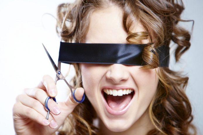 девушка разрезает чёрную повязку на глазах