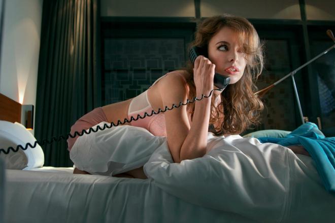Девушка в постели с трубкой телефона в руке