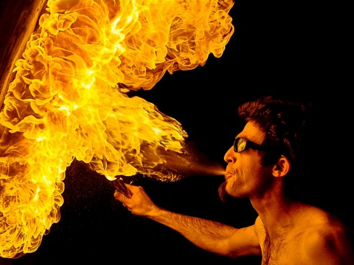 мужчина в солнечных очках дышит огнём
