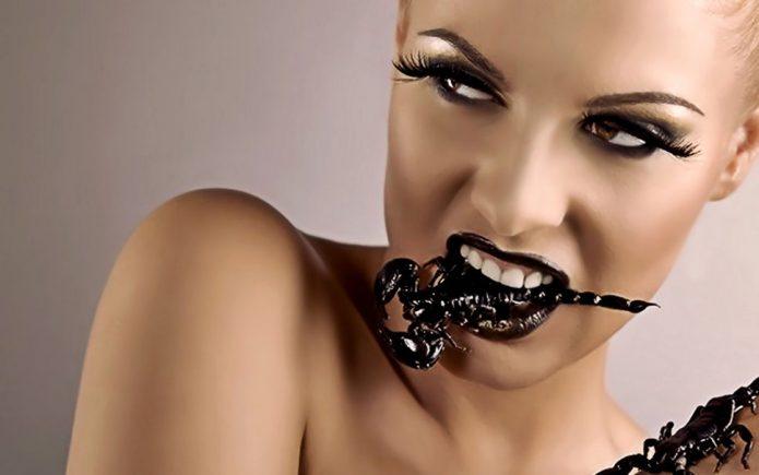 Девушка хищно ест скорпиона